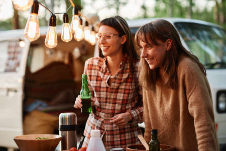 Two young women drinking beers and having fun outdoors on a picnic