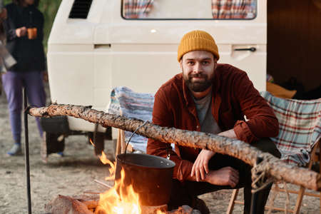 Portrait of young bearded man looking at camera while cooking food on a fire during camping in the forest
