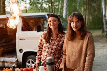 Portrait of young women smiling at camera while spending time on a picnic in the forest