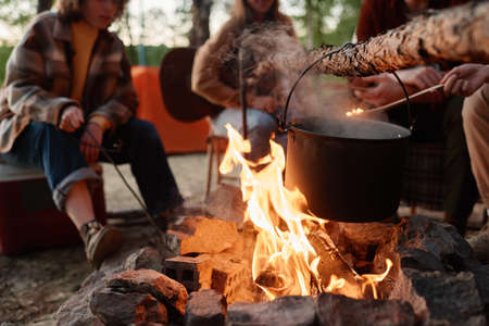 Close-up of food preparing in a pot on a fire with people sitting in the background Stockfoto