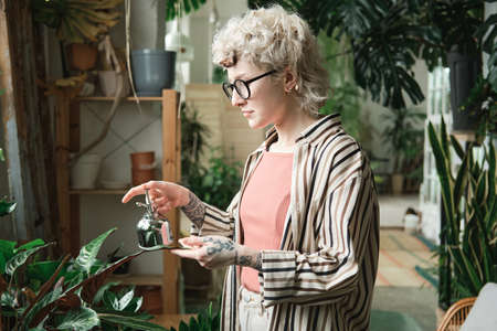 Young woman in eyeglasses caring about plants and waterig them in the garden