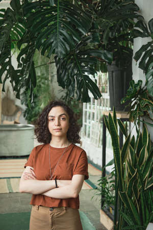 Portrait of young beautiful woman with curly hair looking at camera while standing in botany garden