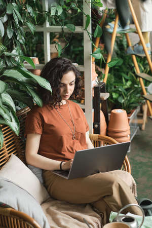 Young businesswoman sitting on sofa and working online on laptop among green plants in the garden