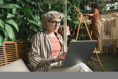 Young businesswoman in eyeglasses sitting on sofa and working online on laptop in the flower shop with her colleague in the background Stockfoto