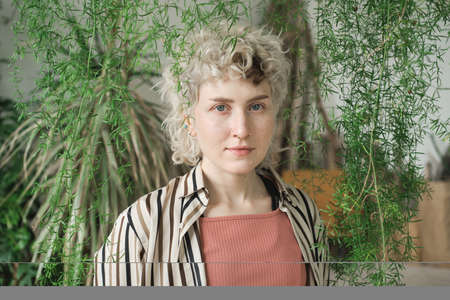 Portrait of young woman with blonde curly hair looking at camera standing among green plants Stockfoto