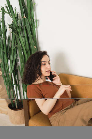 Young woman having conversation on mobile phone while resting on the armchair