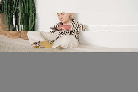 Young woman sitting on the floor near the exotic plants and typing a message online on her mobile phone