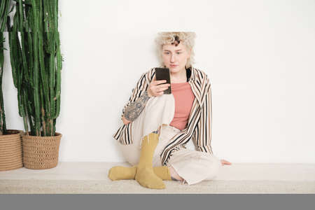 Young elegant woman sitting on the floor and reading online on mobile phone Stockfoto