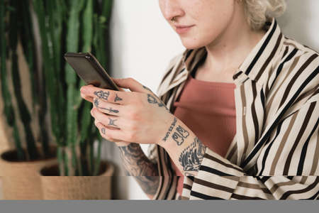 Close-up of young woman with tattoos on her hands holding mobile phone and working online Stockfoto