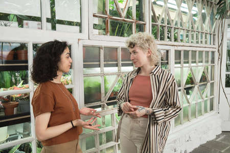Two young women talking to each other and discussing plants while working in botany garden