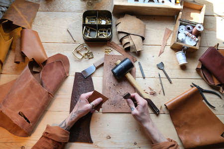 High angle view of worker working with leather and work tools at his table in workshop Stockfoto