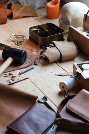 Close-up of working tools and leather textile on the table of carpenter in the workshop