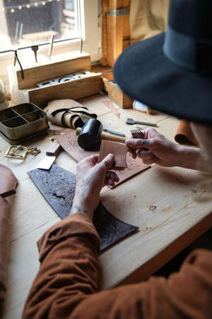 Close-up of carpenter sitting at the table and working with leather, he repairing products