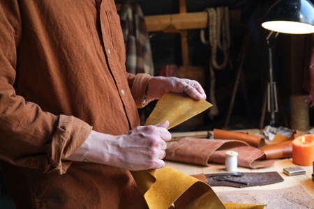Close-up of worker holding leather textile and making products from it in the workshop