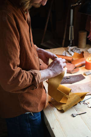 Close-up of craftsman holding pieces of leather textile in his hands and making products in workshop