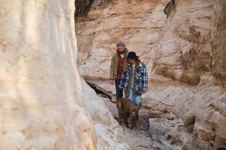 Young couple walking together with their dog along the rocks outdoors