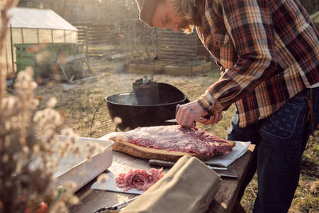 Young farmer cutting big slice of meat with knife at the table outdoors, he preparing meat for barbecue