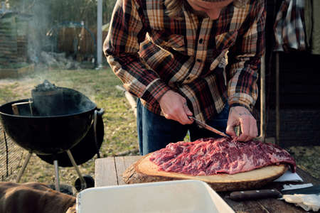 Close-up of man cutting meat at the table for barbecue outdoors