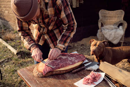 Young farmer cutting fresh meat for barbecue with his dog standing near by and watching for the process