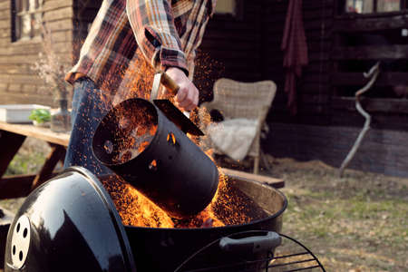 Close-up of young man adding coals in barbecue and lighting it outdoors Stockfoto