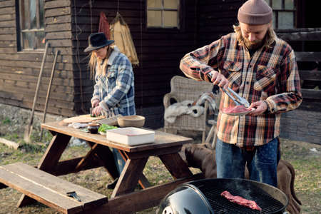 Young man frying meat on barbecue with woman cutting vegetables for salad in the background, they spending time outdoors Stockfoto