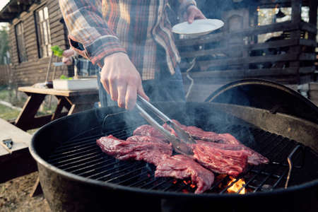 Close-up of young man frying slices of meat on barbecue for dinner outdoors
