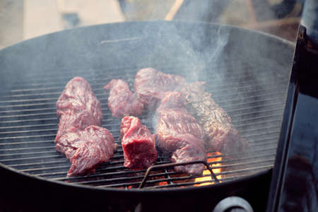 Close-up of slices of meat lying on barbecue grid and frying for dinner