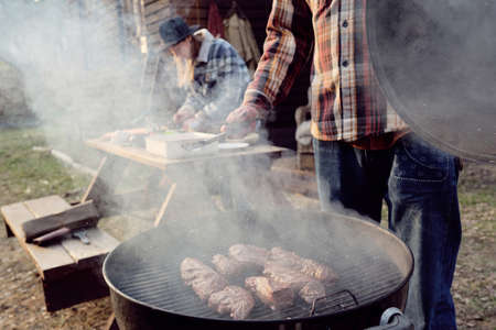 Young man frying meat on barbecue grill with woman cooking at the table in the background outdoors Stockfoto