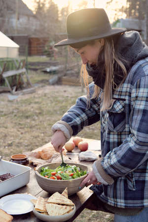 Young woman standing at the table and preparing vegetable salad for dinner outdoors