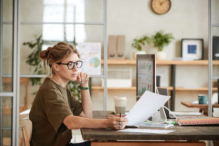 Young businesswoman sitting at her workplace in front of computer monitor and working with documents at office