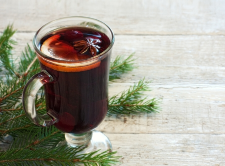 Winter background with glass of mulled wine