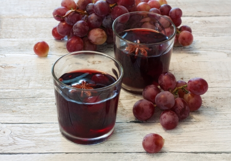 stil: Mulled wine in glasses and red grapes over wood background