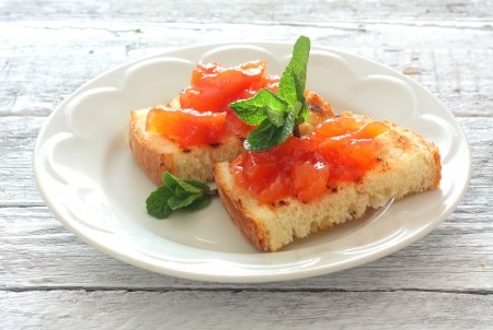 Toasts with fruit jam in white plate over wood background
