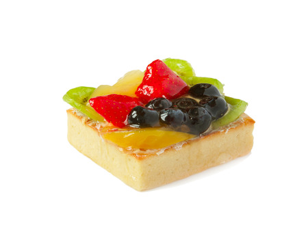 Fruit cakes with fresh strawberry, orange, kiwi and blueberries over white background photo