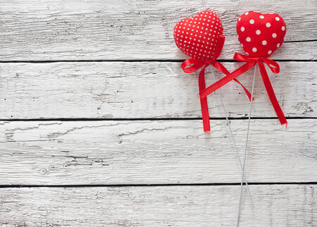 Toy hearts over grunge wood background photo