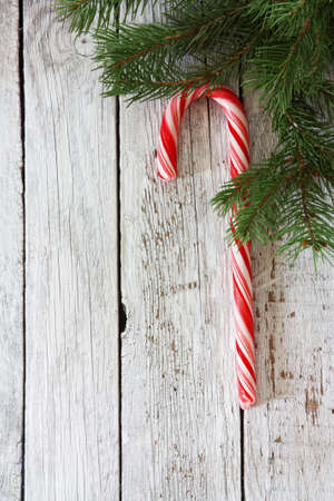 Christmas wood background with lollipop cane and fir branches photo