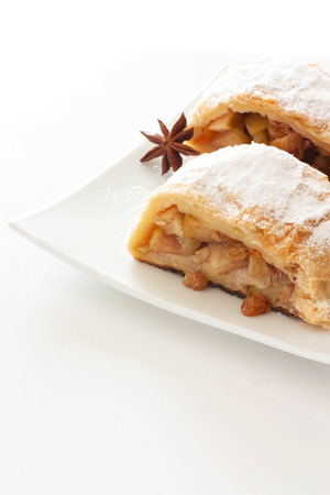 Apple strudel on white plate over white background