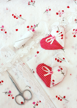 Scrapbooking craft materials - laces, hearts, over cloth background with floral pattern photo