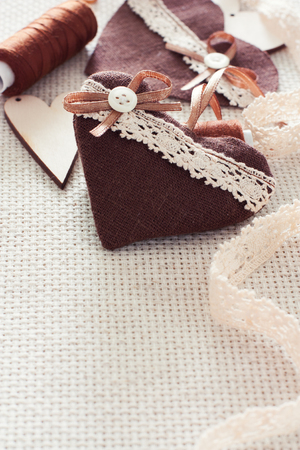 Scrapbook elements - hearts, laces, spool of thread over canvas background photo