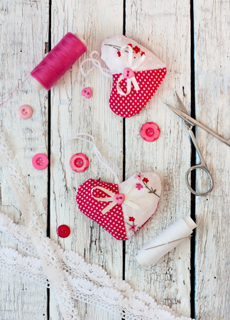 Scrapbook set for Valentines Day- hearts, spoos lof thread,scissors, buttons, laces over old wood background photo