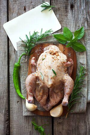 Ruwe gehele kip met groenten op de houten tafel