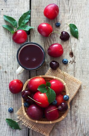 vitamines: Ripe cherry-plums, cherries , blueberries  and cup of juice over natural wood background