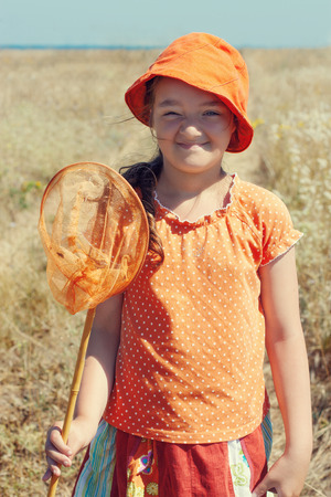 butterfly net: Portrait of kid girl with butterfly net over rural landscape Stock Photo