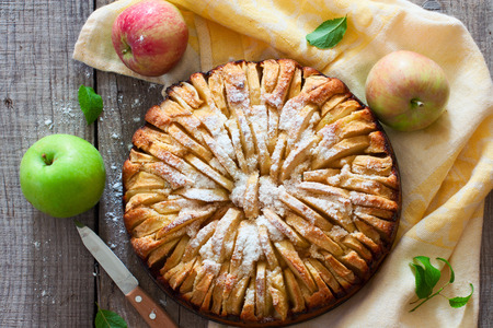 Fresh baked apple pie on the natural wood background