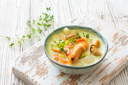 Soup with vegetables, mussels and shrimp in ceramic bowl over white wood background Stock Photo
