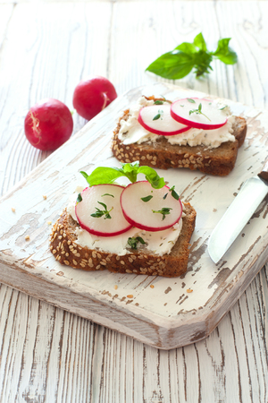 Toasts with ricotta, slices of redish and cucumber over wood cutting board