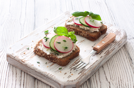 caper: Toasts with rye bread, ricotta, radish and cucumber over wood cuting board