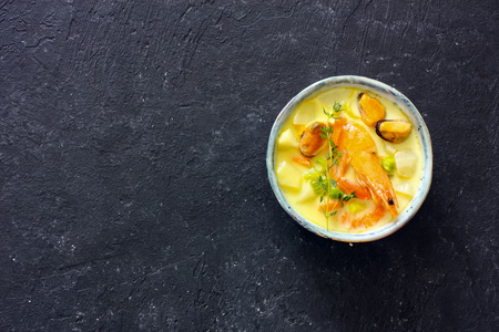 Soup with seafood, potatoes and cream over black atone background. Top view. Copy space