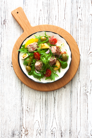 Vegetable salad with grilled tuna ( Nicoise), lettuce, tomatoes and olives  in white plate over white wood background. Top view. Space for text. Rustic style