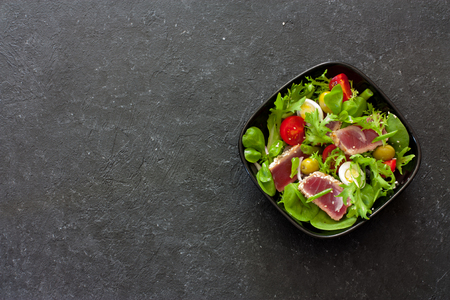 Vegetable salad with grilled tuna ( Nicoise), lettuce, tomatoes and olives  in black plate over black stone background. Top view. Space for text